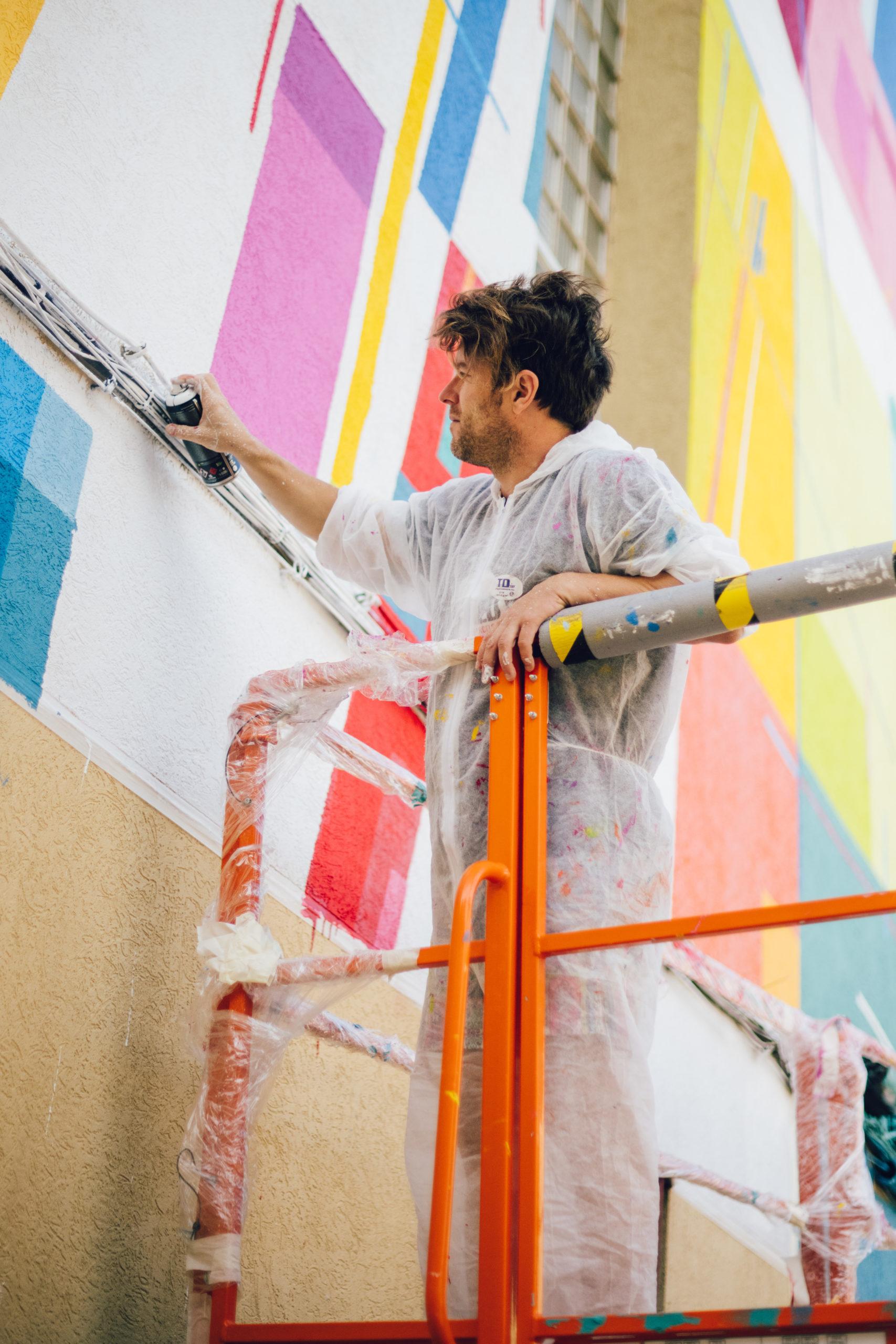 Artista Kenor pintando mural