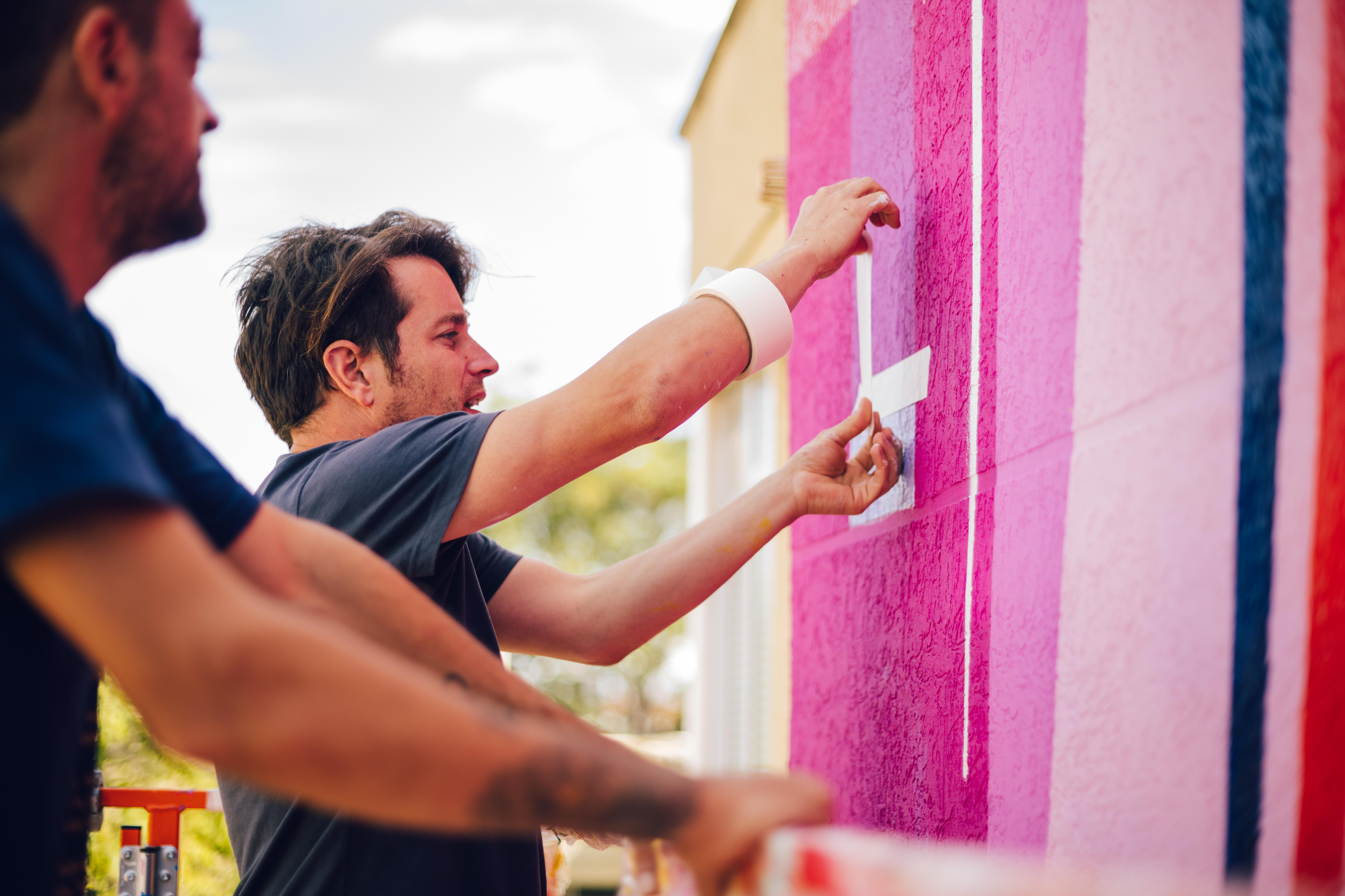 Artista trabajando en un mural artístico en Hospitalet